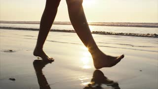 low-section-footage-of-woman-walking-on-wet-sand-slow-motion-video-of-female-with-bare-feet-on-shore-during-sunset-tracking-shot-of-woman-spending-leisure-time-sunlight-is-reflection-on-seascape_vdgp8